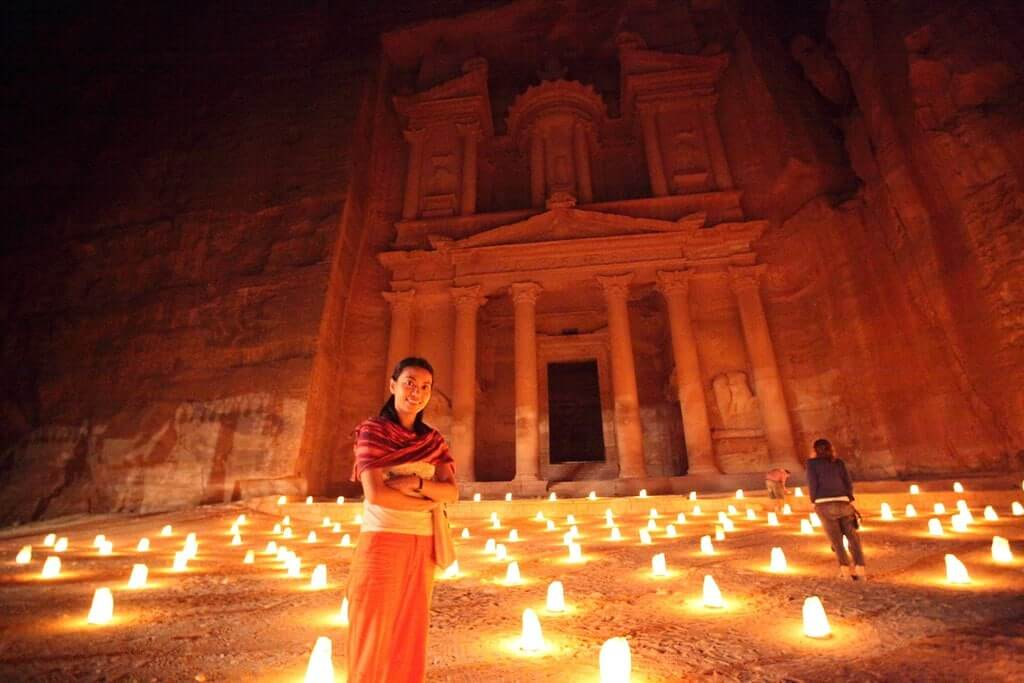 Donna sorridente davanti al Tesoro illuminato da candele luminose per il Petra by Night.